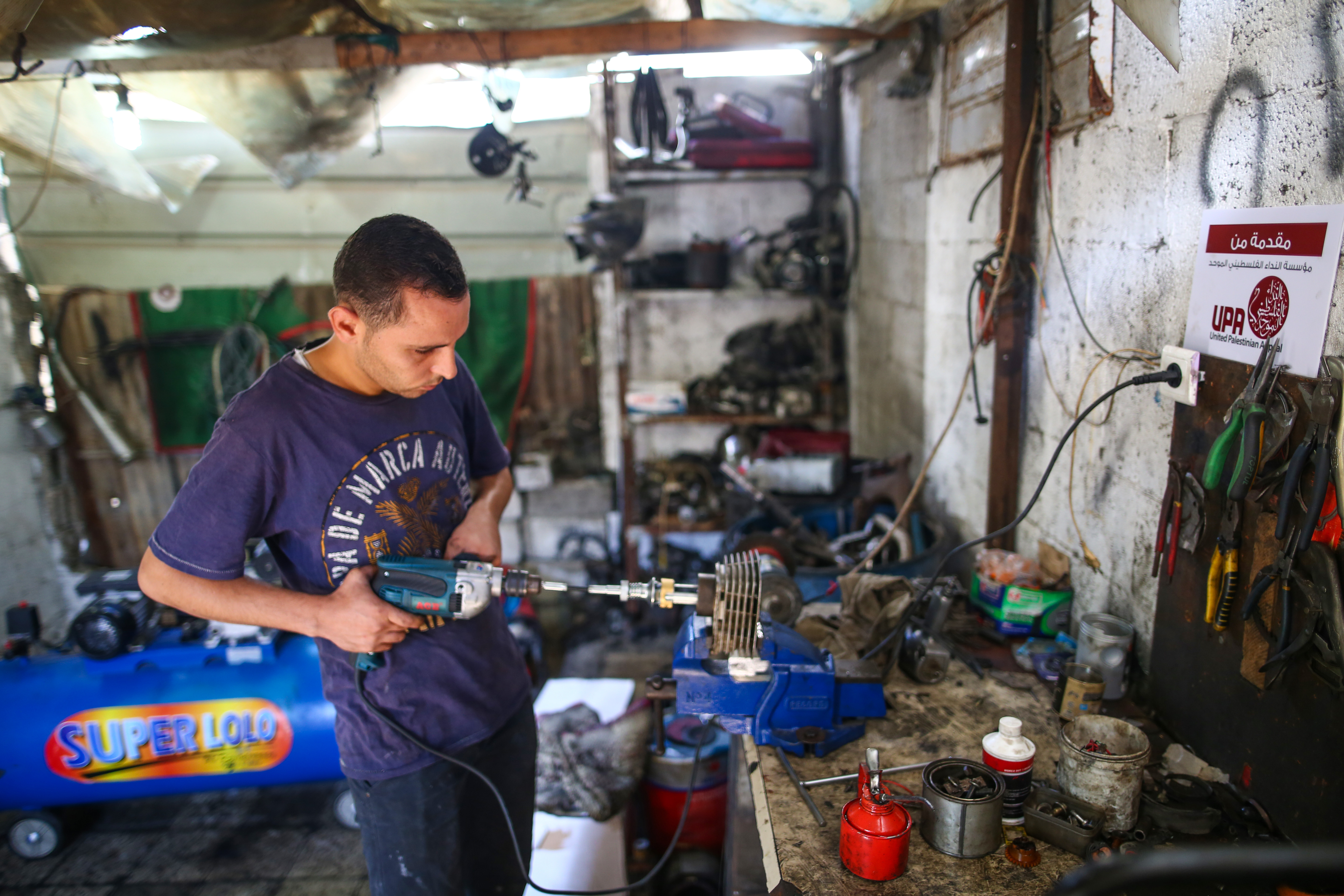 Mohammed works in his mechanic shop.