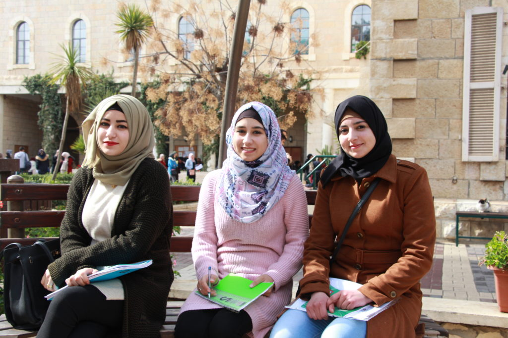Students sitting outside Bethlehem University.
