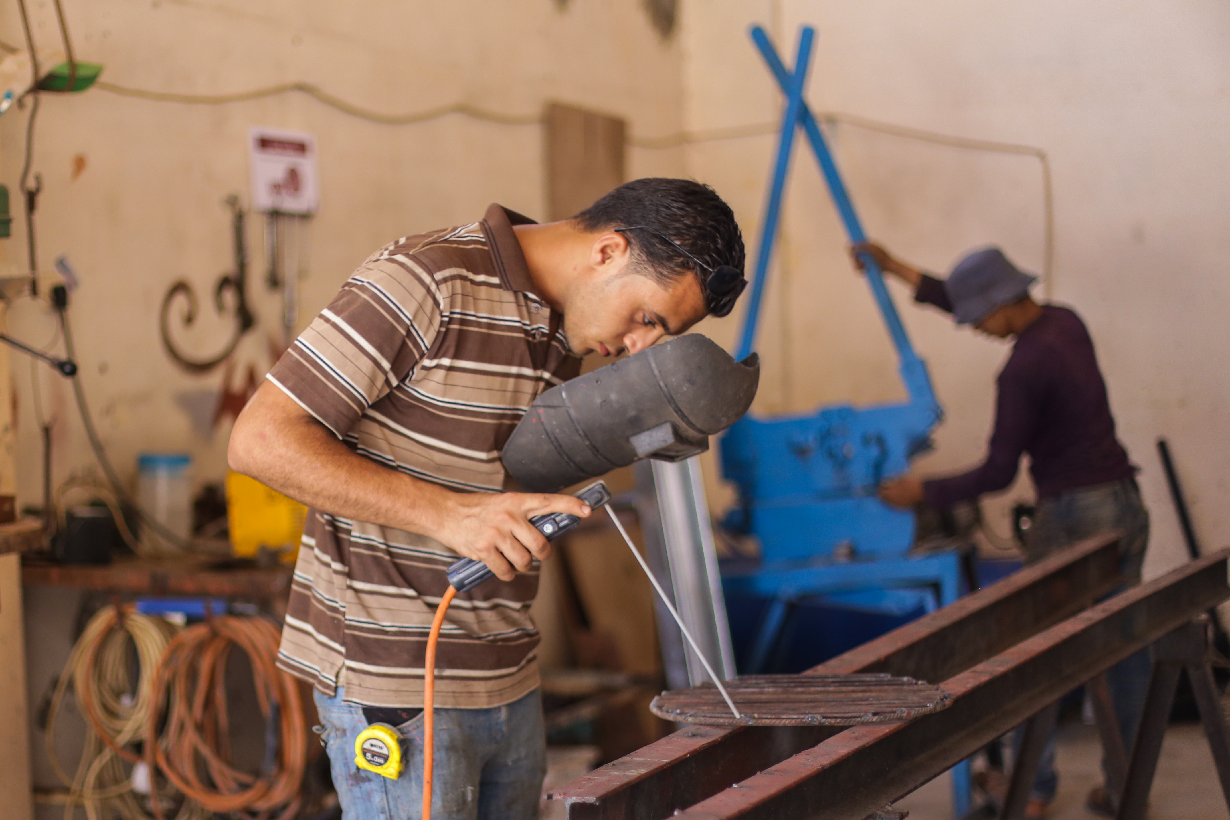 Hamdi works in his metal shop in Gaza.