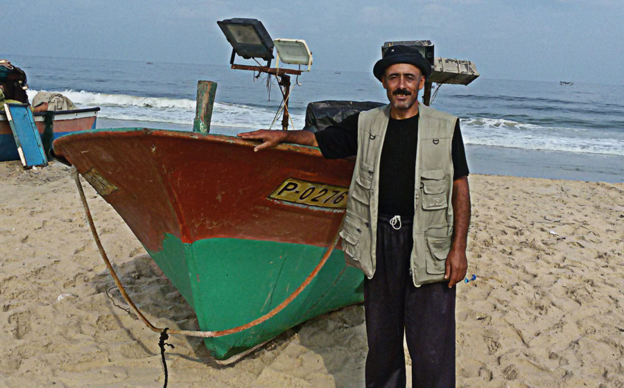 Adel Ferwana stands near his fishing boat in Gaza.